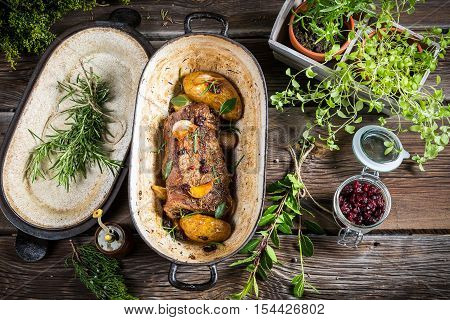 Roasted venison with herbs and vegetables on wooden table