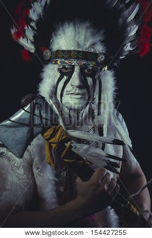 Geronimo, American Indian chief with feather headdress and traditional war ax