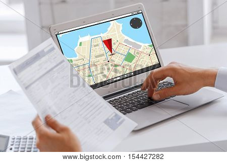 business, navigation, technology and people concept - businessman with gps navigator map on laptop computer screen working at office