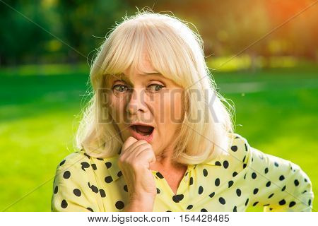 Senior woman with open mouth. Lady holding her chin. Developing the idea. Familiar things from new perspective.