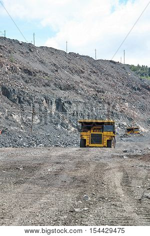Iron ore opencast road with heavy mining dump trucks driving along it