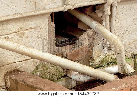 Close up of broken wall plumbing pipes and drain requiring mainenance and repair