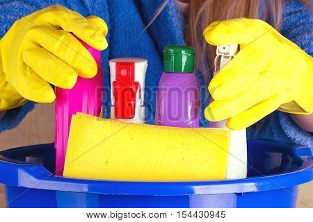 close-up of caucasian woman holdinh basin with cleaning supplies