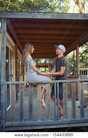 loving couple on the terrace of the wooden rest house. Sincere interest in topic. Listening with deep interest. Caucasian brunette is sitting on the handrail and hugging her husband