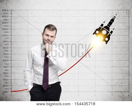 Doubtful businessman in red tie is standing near concrete wall with graph and rocket sketch on it. Concept of launching a new project.
