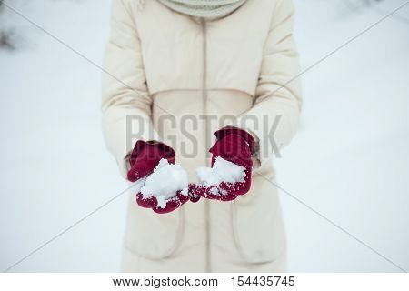winter girl throwing snowball at camera smiling happy having fun outdoors on snowing winter day playing in snow. Cute playful multicultural Asian Caucasian young woman outdoor enjoying first snow.
