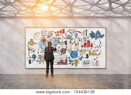 Rear view of man drawing colorful startup sketch on whiteboard in room with geometric ceiling. Concept of business planning. 3d rendering. Toned image
