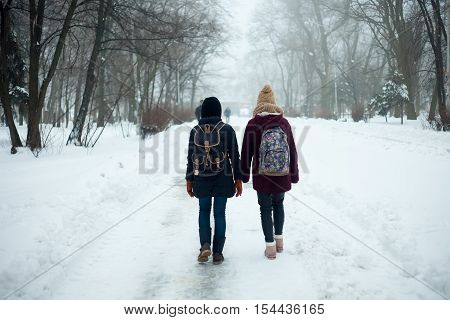 couple man carries a girl in winter. Couple holding each other's hands the winter goes on the road enjoying a stroll. fashion lifestyle. going through the park holding hands in the winter.