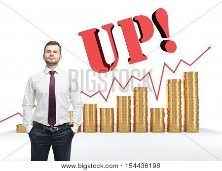 Confident man standing near stacks of giant coins red graph and the word up. Concept of capitalization of company