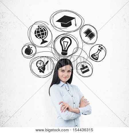 Smiling girl with black hair is standing near white wall with education sketches on it. Concept of further education