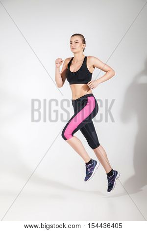 Young beautiful woman in fitness wear running