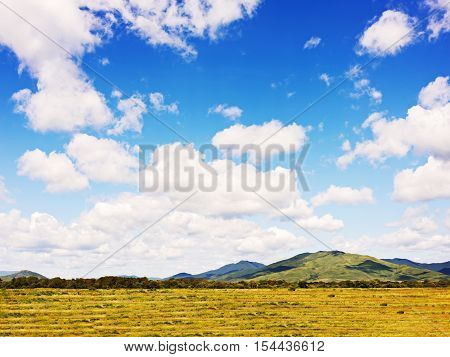 Landscape with mountain views, arable land, blue sky and beautiful clouds. Real scene without any light effects.