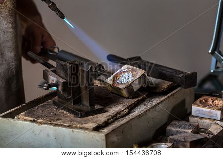 Melting Silver Grains to liquid state in crucible with blowtorch; Goldsmith Workshop