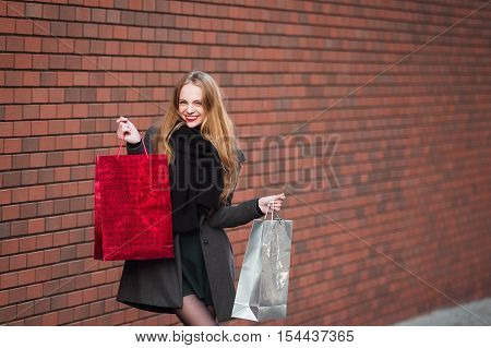 Sale, consumerism and people concept - happy young beautiful women holding shopping bags, walking away from shop