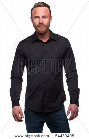 Wealthy confident relaxed young man in black shirt and denim jeans looking at camera isolated over white studio background