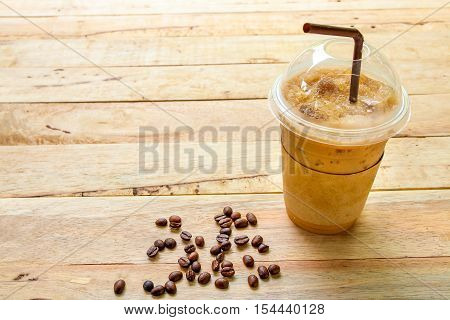 Iced Coffee In Plastic Glass On Wooden  Background