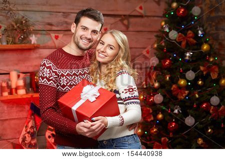 Lovely christmas couple holding present. Stylish happy cheerful people on christmas tree background