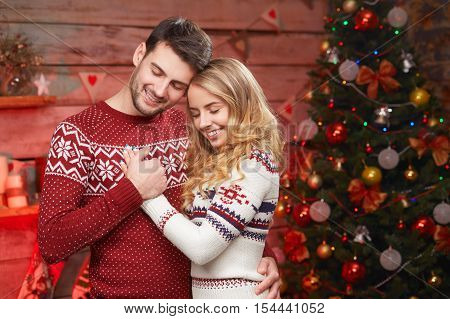 Young happy couple dreams on Christmas Night. Young blond woman and handsome man embracing and dreaming near christmas tree