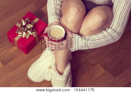 Close up of woman's hands holding a cup of hot coffee sitting on the floor enjoying the holiday morning time