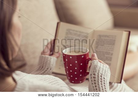 Young woman lying on the living room sofa reading a book and holding a cup of hot coffee