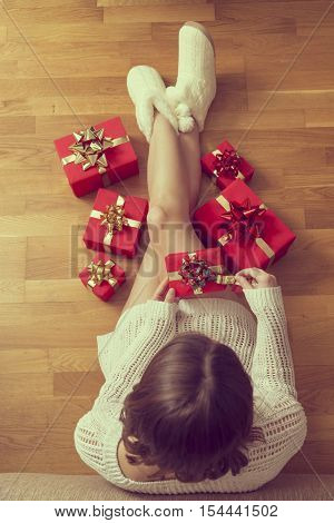 Young woman wearing a sweater and house boots sitting on the floor unwrapping nicely decorated presents
