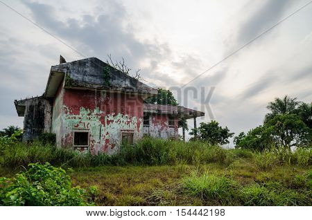 Ruined mansion surrounded by lush green with dramatic sky. Traces of the civil war in Liberia.