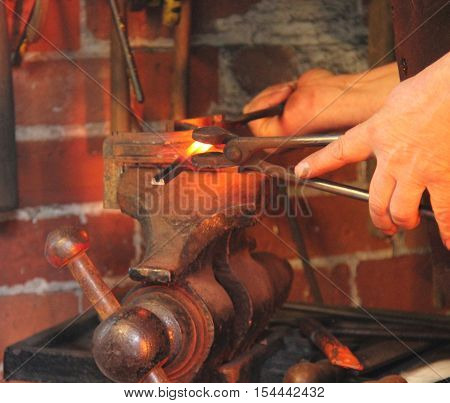 A Blacksmith Working With Red Hot Metal in a Vice.
