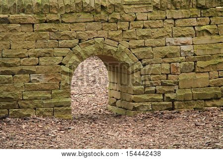 A Stone Built Wall with a Small Archway Through It.