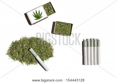 Rolled cigarettes with cannabis.Cannabis gathered in pile and in two matchboxes lays on the white table with rolled cigarettes with hemp.