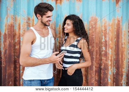 Happy multiethnic young couple listening to music from cell phone with earphones