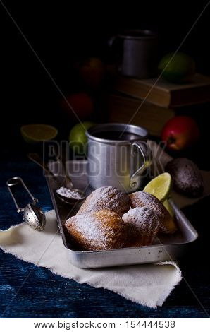 Homemade biscuits madeleines with powdered sugar on a dark background. Selective focus.