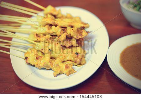 Grilled pork served with peanut sauce or sweet and sour sauce (pork satay); Filtered image processed vintage effect.