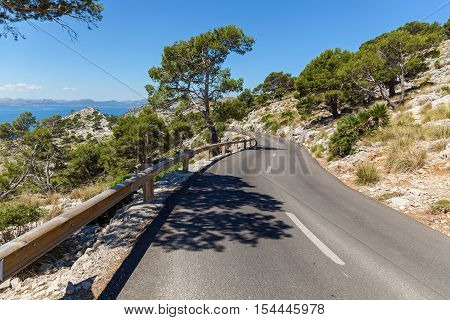Road to the beach. Asphalt road on the rocky coast of Mallorca that leads to the beach.