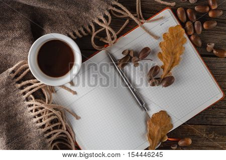 coffee mugs in autumn background with notebok