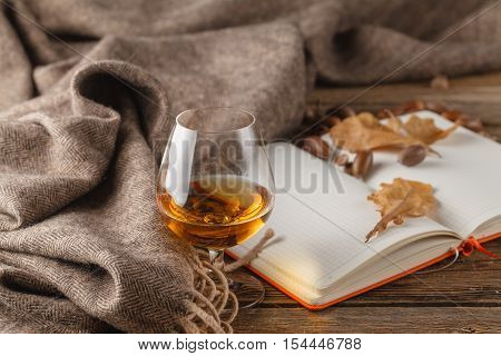 Open Notepad With Empty White Pages And Warm Scarf On Wooden Background With Autumn Leaves, Top View