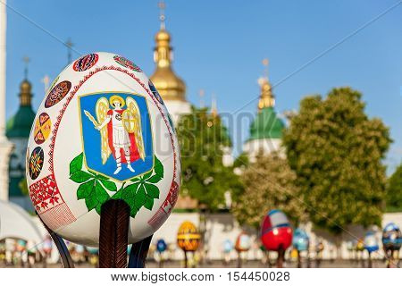 Kyiv Ukraine Sophia Square 2 of May 2016. Emblem on the Easter egg. Macro shot of the Easter painting egg with national emblem against St. Sophia Cathedral in Kyiv.