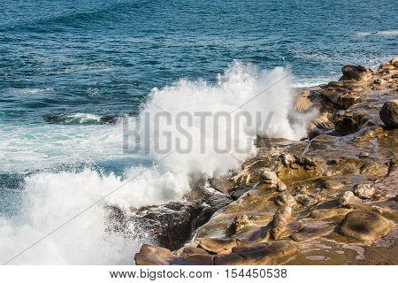 Crashing waves on La Jolla Cove rocky beach in San Diego