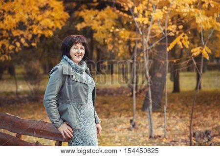 Mature woman is walking in the pak and smilling