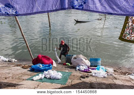 DHAKA BANGLADESH- JUNE 25 2016. Unidentified washerman wash their cloths in the river