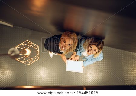 High angle shot of two female colleagues working on a tablet.