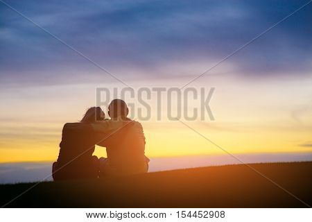 Couple on evening sky background. People sitting and hugging. We found each other. On top of the world.