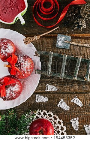 Little white powder footprints and tools of elf, dwarf or brownie on the christmas table with candy apples