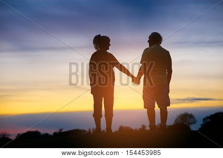 Two people holding hands. Back view of standing couple. Time is nothing. Be with me.