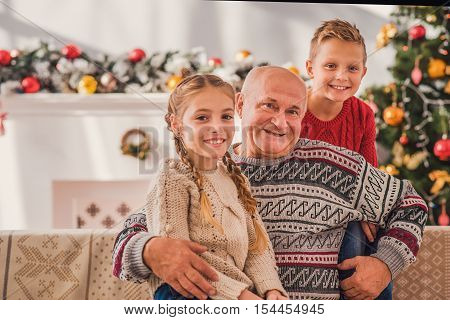 Joyful old grandfather is celebrating Christmas with his grandchildren. He is sitting on couch and holding girl. They are looking at camera and smiling