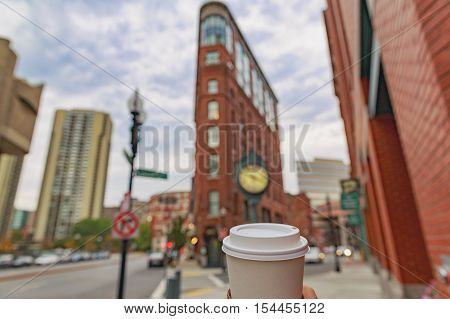 cup of coffee on a background of Boston. triangular Flatiron Building. walking around historic downtown Boston with coffee in hand. the concept of sightseeing, tourism and traveling. blurred background