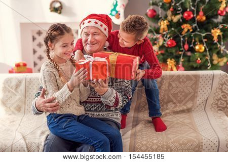 Merry Christmas. Joyful old man is giving presents to his grandchildren. He is sitting on couch at home and holding girl on knees. Boy is embracing him and laughing