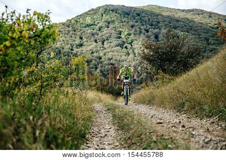 Privetnoye Russia - September 22 2016: male rider cyclist riding uphill on a forest trail during Crimean race mountainbike