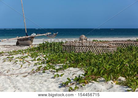 Indian Ocean coastline. Indian Ocean coastline with the sandy beach covered with coastal plants with some construction and boat.fishing tackle