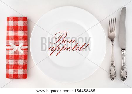 Bon appetit! Poster with a vintage cutlery, plate and a checkered napkin on a white background