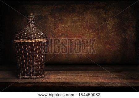 vintage brown background Wicker bottle of wine on the shelf
